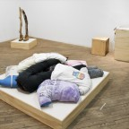 Installation view: Feminist Body Pillow (2013), Hand printed t-shirts, jeans; Music vitrine; There is a group, if not alliance, walking there too, whether or not they are seen (2013), Driftwood, work boots, socks. By Ginger Brooks Takahashi and courtesy of the artist. Image courtesy of Vox Populi.