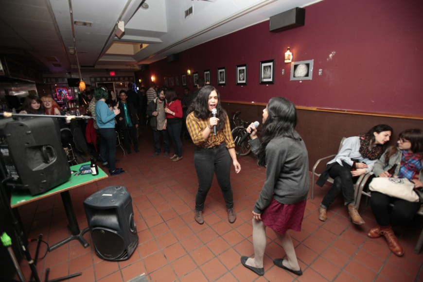 Members of the crowd at Teri's Bar singing and enjoying an evening of Karaoke highlighting women artists hosted by Sara Sherr