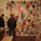Visitors looking at the flyer wall during the opening night of the Alien She exhibition.