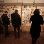 Visitors looking at the collection of original zines on the zine wall during the opening night of the Alien She exhibition.