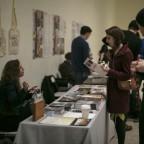 Artist Stephanie Bursese talks to visitors to the Vox Populi Gallery table at the Philadelphia Photo Arts Center Book Fair